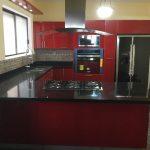 cocina de acrilico rojo con cubierta de granito y torre de horno