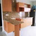 cocina de aglomerado con barra desayunadora y cubierta de granito